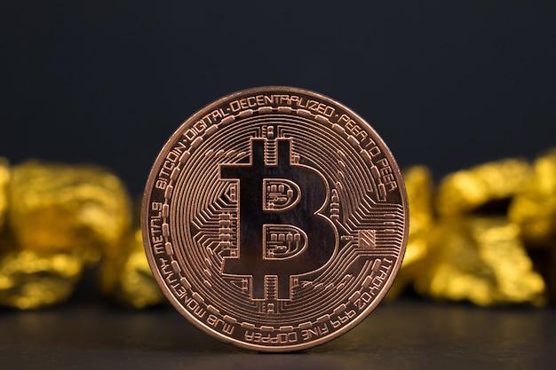 Nahaufnahme von bitcoin digitaler währung und goldnugget auf schwarzem hintergrund