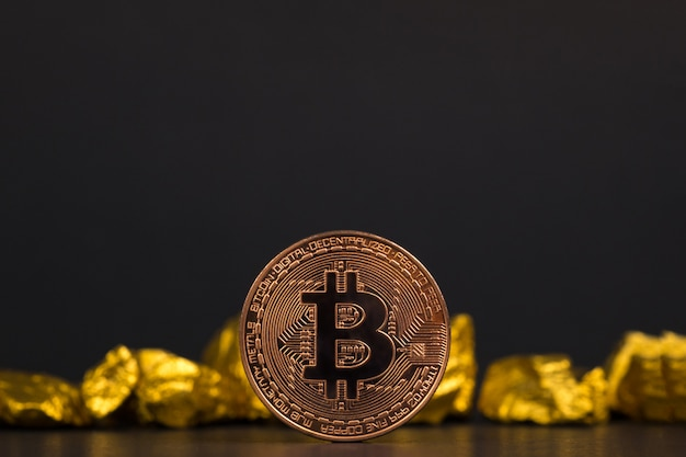 Nahaufnahme von bitcoin digitaler währung und goldnugget oder golderz auf schwarzem hintergrund, edelstein oder klumpen des goldenen steins