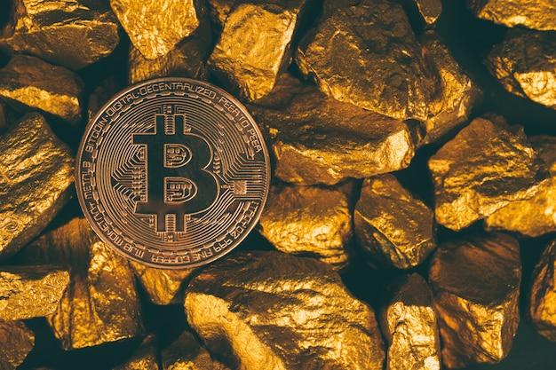 Nahaufnahme von bitcoin digitaler währung und goldnugget oder golderz auf schwarzem hintergrund