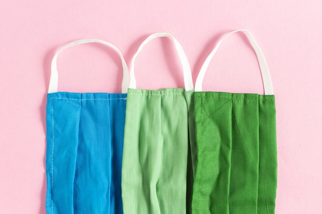 Nahaufnahme von blauen, hellgrünen und dunkelgrünen gesichtsschutzmasken auf rosa