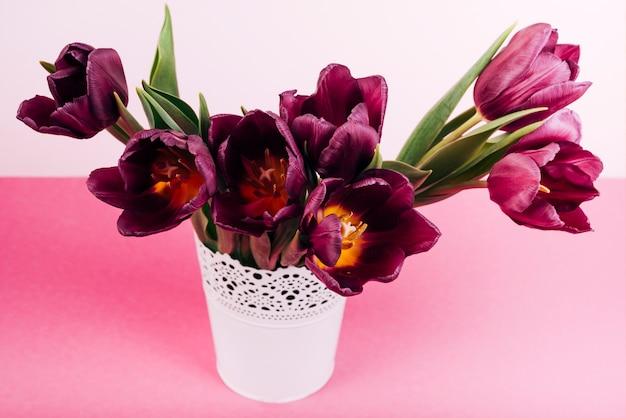 Nahaufnahme von blühenden tulpen im weißen vase auf rosa tabelle