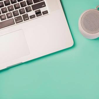 Nahaufnahme von bluetooth lautsprecher und laptop auf grünem hintergrund