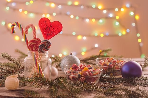 Nahaufnahme von bonbons in schalen auf dem tisch mit weihnachtsschmuck verziert