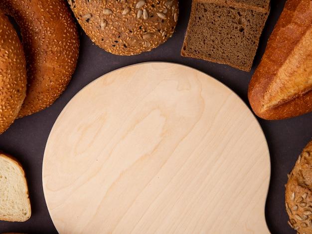 Nahaufnahme von broten als bagel-cob-roggenbrot-baguette mit schneidebrett auf kastanienbraunem hintergrund