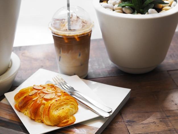 Nahaufnahme von brotmandeln mit gabel und messer über weißem teller auf dem buch und einem glas eiskaffee im café. frühstück am morgen oder kaffeepause.