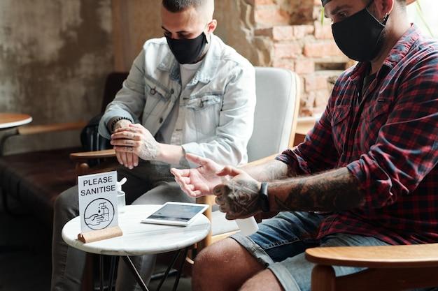 Nahaufnahme von brutalen männern in masken, die in kleinem café sitzen und hände mit desinfektionsmittel reinigen