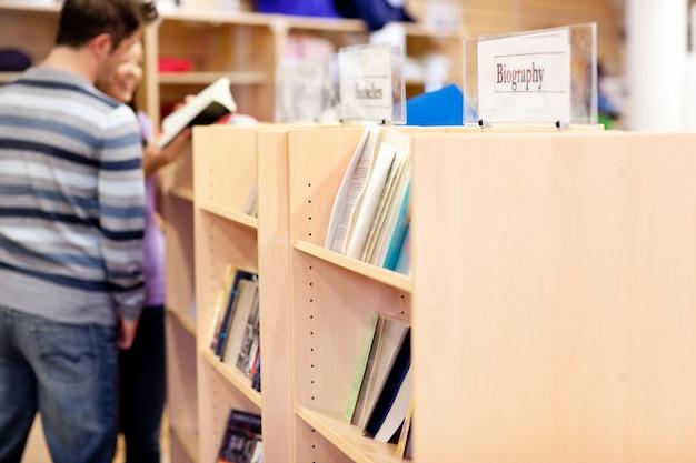 Nahaufnahme von bücherregalen in einer bibliothek mit studenten lesebuch