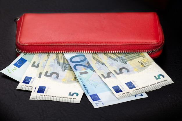 Nahaufnahme von bündeln von euro-banknoten und öffnen einer roten brieftasche auf dunklem hintergrund. selektiver fokus.