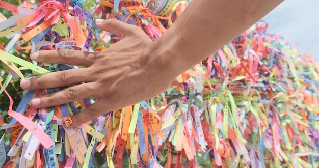 Nahaufnahme von bunten bändern in bahia, brasilien. mannhand, die eine anfrage mit brasilianischen bändern macht. glaube.