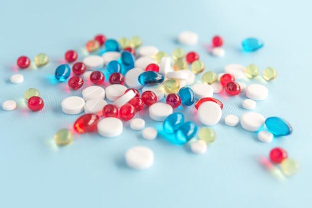 Nahaufnahme von bunten kapseln und weißen tabletten