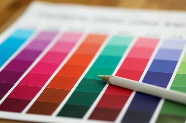 Nahaufnahme von bunten palettenproben und weißem bleistift auf arbeitstisch. farbführer der farbe. regenbogenkatalog. innendekoration und renovierungskonzept