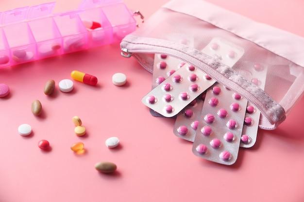 Nahaufnahme von bunten pillen und blisterpackung auf rosa hintergrund