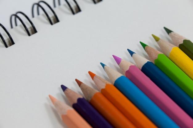 Nahaufnahme von buntstiften und notizbuch