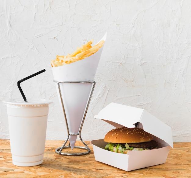 Nahaufnahme von burger; pommes frites und entsorgung tasse auf schreibtisch aus holz
