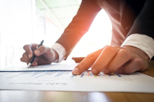 Nahaufnahme von business-mann hand arbeiten auf laptop-computer mit business-grafik-informations-diagramm auf holztisch als konzept