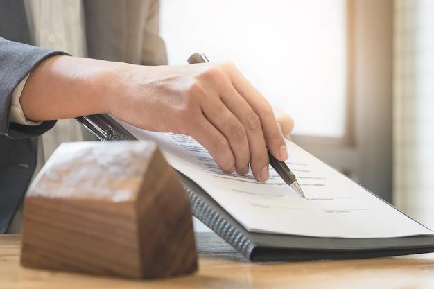 Nahaufnahme von business mann zeigen und unterzeichnung vereinbarung für den kauf haus. bankmanager konzept.