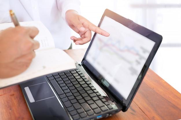 Nahaufnahme von business-teamarbeit diskutieren daten mit einem finanz-diagramm auf laptop-computer auf einem schreibtisch.