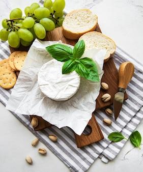Nahaufnahme von camembertkäse, traube, nüssen und honig auf schneidebrett auf weißer tischplatte