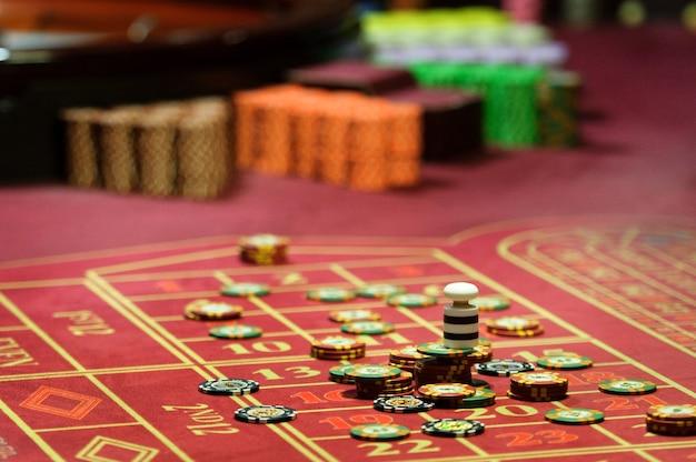 Nahaufnahme von casino-chips auf dem roten tisch