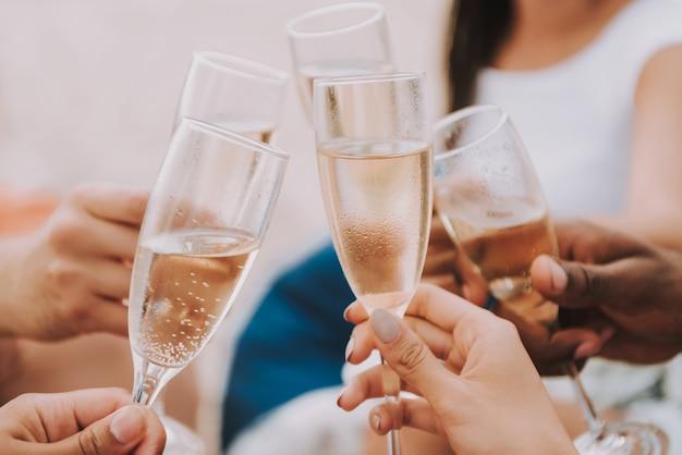 Nahaufnahme von champagne glasses cheering im sun.