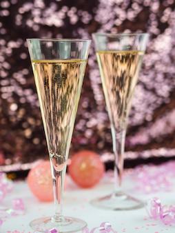 Nahaufnahme von champagnergläsern mit rosa kugeln