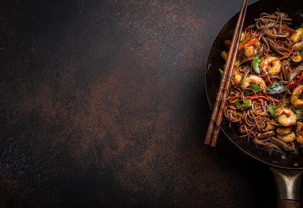 Nahaufnahme von chinesischen soba-stir-fry-nudeln mit garnelen, gemüse in alter rustikaler wok-pfanne, serviert auf konkretem hintergrund, nahaufnahme, draufsicht. traditionelles asiatisches/thailändisches gericht, platz für text