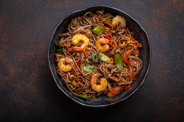 Nahaufnahme von chinesischen soba-stir-fry-nudeln mit garnelen, gemüse in rustikaler keramikschale, serviert auf betonhintergrund, nahaufnahme, draufsicht. traditionelles asiatisches / thailändisches gericht, mahlzeit im chinesischen stil