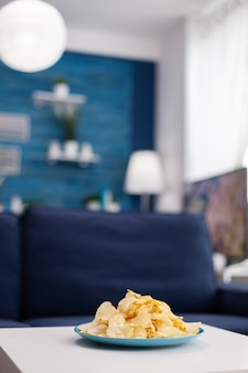 Nahaufnahme von chips snack auf couchtisch sitzen. modernes wohnzimmer mit niemandem herein mit blauen möbeln und wänden, schön verziert ziemlich einfache einrichtung der wohnung. elegante retro-dekoration, gemütlich.