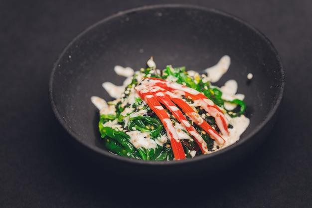 Nahaufnahme von chuka-salat serviert in einer weißen schüssel, vertikaler schuss, dunkelbrauner steinhintergrund.