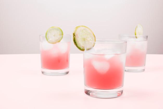 Nahaufnahme von cocktails auf dem rosa schreibtisch gegen grauen hintergrund