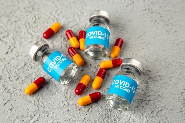 Nahaufnahme von covid-impfstoffpillen auf grauem wellenhintergrund mit freiem speicherplatz