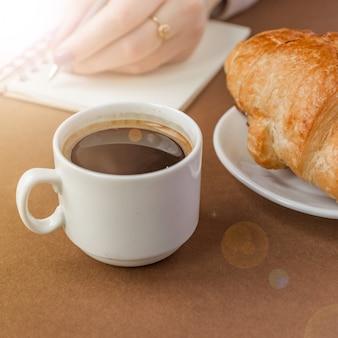 Nahaufnahme von croissant und espresso. frauenschreiben auf notizbuch. freiberufler bei der arbeit