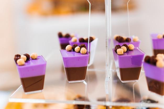 Nahaufnahme von cupcakes mit sahne und nüssen auf einem transparenten ständer.
