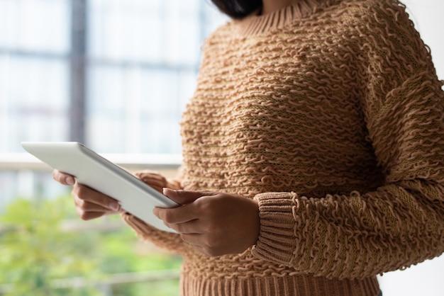 Nahaufnahme von dame in gestricktem aufpassendem video der strickjacke auf tablette
