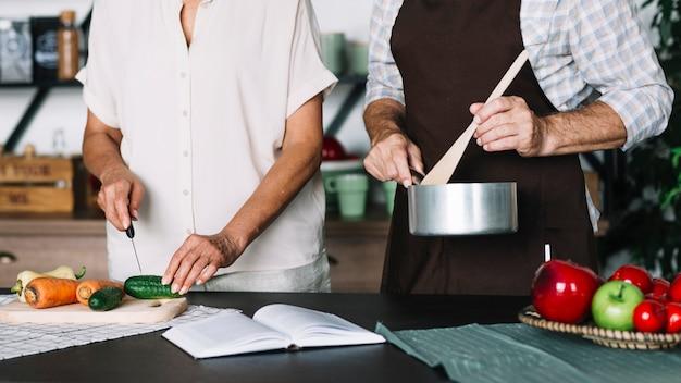 Nahaufnahme von den älteren paaren, die lebensmittel in der küche vorbereiten