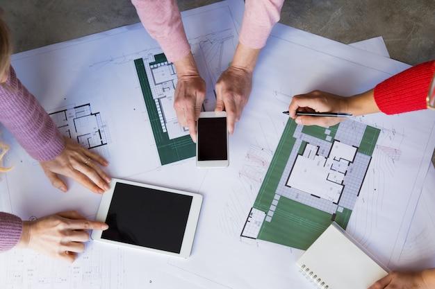 Nahaufnahme von den architekten, die mit zeichnungen am schreibtisch arbeiten
