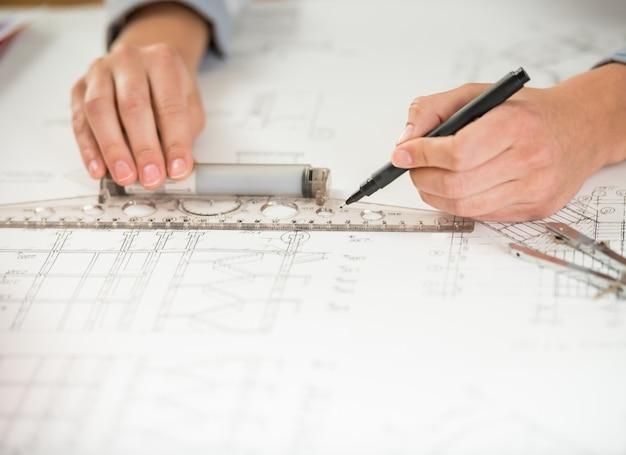 Nahaufnahme von den designerhänden, die mit architekturplan arbeiten.