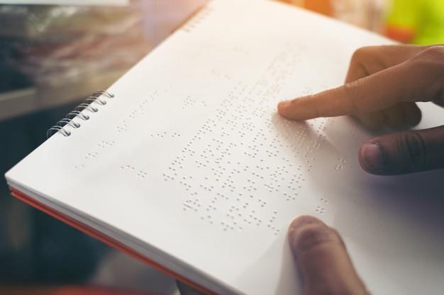 Nahaufnahme von den fingern, die blindenschrift, hand einer blinden person liest etwas blindenschrifttext eines blindenschriftbuches lesen.