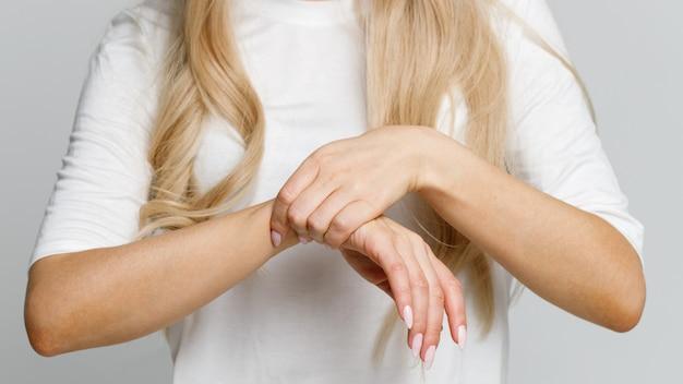 Nahaufnahme von den frauenarmen, die ihr schmerzliches handgelenk verursacht durch verlängerte arbeit am computer halten