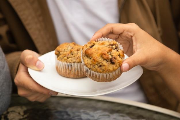 Nahaufnahme von den freunden, die kleine kuchen essen