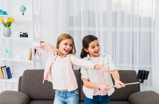 Nahaufnahme von den freundinnen, die selbstporträt am intelligenten telefon im wohnzimmer nehmen