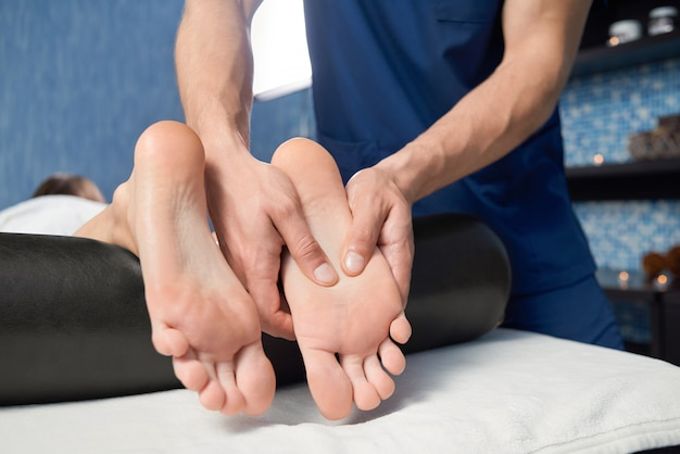 Nahaufnahme von den händen des masseurs fuß der frau im badekurort massierend