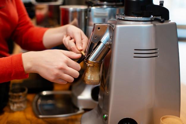 Nahaufnahme von den händen, die an kaffeemaschine arbeiten