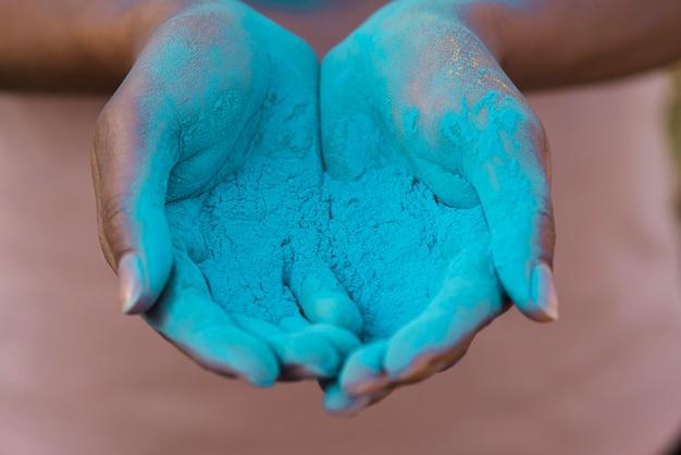 Nahaufnahme von den händen, die blaues pulver halten