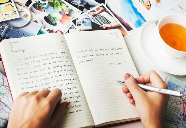 Nahaufnahme von den händen, die ein tagebuch schreiben