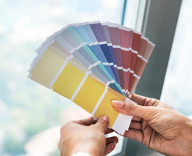 Nahaufnahme von den händen, die farbmuster halten