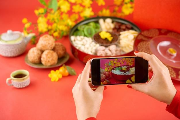 Nahaufnahme von den händen, die fotos von tet feiertagslebensmittel auf smartphonekamera machen