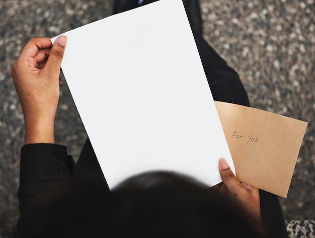 Nahaufnahme von den händen, die leeres papier halten