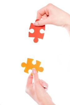 Nahaufnahme von den händen, die versuchen, kleine puzzlen anzuschließen.