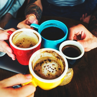 Nahaufnahme von den händen, die zusammen kaffeetassen halten